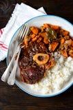 Osso buco炖牛肉用在西红柿酱的煮沸的米与葱、红萝卜、芹菜、大蒜、迷迭香和月桂树叶子 免版税图库摄影