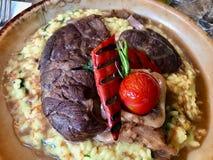 Osso Buco, Kalbfleisch-Schäfte, die im Wein mit Safran Risotto, gebratenem rotem Pfeffer und Rosemary gedünstet werden stockfoto