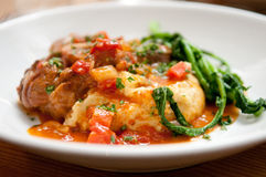 Osso buco made with polenta and a tomato sauce with fresh greens. Osso buco with polenta and a tomato sauce with fresh greens Stock Photography