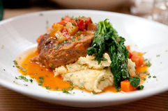 Osso buco with polenta and a tomato sauce with fresh greens Royalty Free Stock Photography