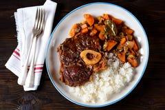 Osso bucokalops med kokta ris i tomatsås med lök-, morot-, selleri-, vitlök-, rosmarin- och lagersidor arkivbilder