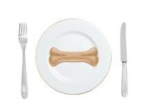 Osso do alimento de cães em uma placa com forquilha e na faca isolada no branco Fotografia de Stock