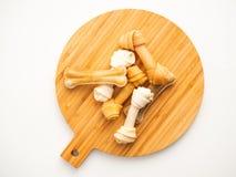 Osso do alimento para cães em desbastar a madeira no branco imagem de stock