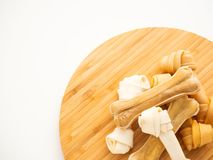 Osso do alimento para cães em desbastar a madeira no branco fotos de stock