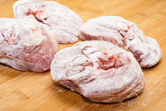 Ossobuco floury on wooden board. Ossobuco floury (bone-in lamb shank steaks) on a wooden chopping board Stock Image