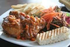 Ossobuco roast lamb. With frenchfries and vegetables Royalty Free Stock Photography