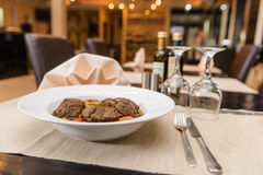 Ossobuco on white plate. Restaurant setup with Ossobuco in white plate and glasses on table Royalty Free Stock Image