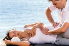 Ostéopathe manoeuvrant la hanche femelle extérieure photo stock