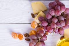 Ost klipper med fikonträd, muttrar, honung, druvor på en träbrädebakgrund royaltyfri bild