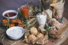 Ost klumpa ihop sig tempura, kryddiga fega vingar och olika mellanmål Arkivbild