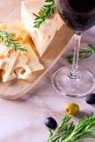 Ost med gröna och svarta oliv och exponeringsglas av rött vin Arkivfoton