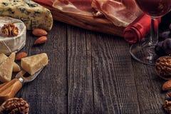 Ost, muttrar, druvor och rött vin på träbakgrund arkivbild