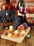 Ost och fikonträd på ett träbräde, rött vin i ett exponeringsglas, druvan och julattribut omkring Royaltyfri Bild