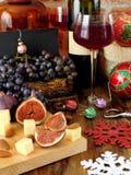 Ost och fikonträd på ett träbräde, rött vin i ett exponeringsglas, druvan och julattribut omkring Arkivfoton
