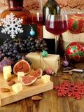 Ost och fikonträd på ett träbräde, rött vin i ett exponeringsglas, druvan och julattribut omkring Arkivfoto
