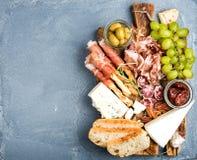 Ost- och köttaptitretareval Prosciuttodi Parma, salami, brödpinnar, bagettskivor, oliv som sol-torkas royaltyfri foto