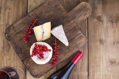 Ost och rött vin Olik ost med den vita och blåa formen Bär av vita blommor för röda vinbär Träbakgrund och frigör Royaltyfria Foton