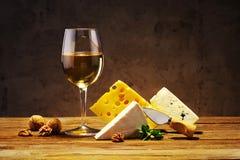 Ost och vin i ett exponeringsglas på ett träbräde royaltyfri fotografi