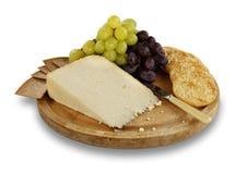 Ost, smällare och druvor på träbräde arkivfoton