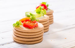 Ost, tomater och gräsplaner på runda kakor Kakalögn på en w Arkivfoton