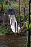 Ostadig träbro över floden Arkivfoton