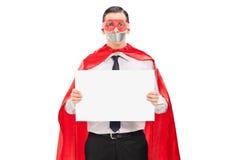 Ostaggio in costume del supereroe che tiene insegna in bianco Immagine Stock