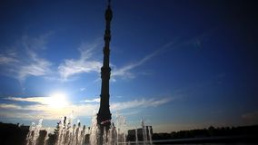 Ostankino TV tower in Moscow. Fountain on. Foreground and sunset sky On background, Reflected in water. Russia stock video