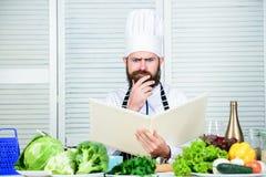 Ostateczny kucharstwo przewdonik krok po kroku Ksi??kowa przepis kopii przestrze? Obs?uguje szefa kuchni w kapeluszu i fartuch cz zdjęcia stock