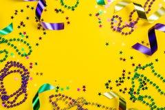 Ostatki karnawałowy pojęcie - koraliki na żółtym tle fotografia royalty free