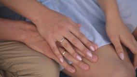 Ostatnio zamężny facet trzyma rękę jego młoda żona obrączki ślubne i palmy zamykają up zbiory