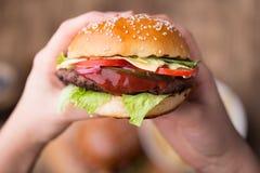 Ostburgare i händer Äta hamburgare royaltyfri fotografi