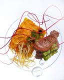 Osteldfast form med slises av grillat kött på vit bakgrund på en genomskinlig platta, slut upp arkivfoto