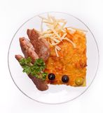 Osteldfast form med slises av grillat kött på vit bakgrund på en genomskinlig platta, slut upp royaltyfri fotografi
