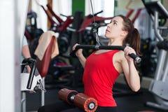 Ostenta a jovem mulher que faz exercícios no gym fotos de stock
