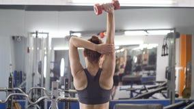 Ostenta a moça que faz o exercício da extensão do tríceps no gym A mulher que guarda o peso livre nas mãos atrás da cabeça abaixa vídeos de arquivo