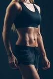 Ostenta o retrato da mulher que veste o sportswear preto sobre a obscuridade foto de stock royalty free