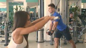 Ostenta os povos que fazem exercícios da força nos simuladores no gym filme