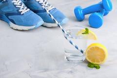 Ostente a composição com água de vidro do material desportivo com limão m Fotografia de Stock