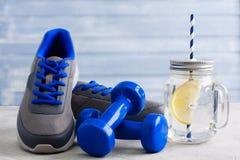 Ostente a composição com o frasco do material desportivo e de pedreiro com limão Foto de Stock