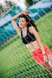 Ostente meninas no short e na parte superior preta levantados perto do objetivo do futebol A jovem mulher 'sexy' ostenta exercíci fotografia de stock