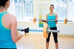 Ostente o conceito de levantamento - jovem mulher que exercita com barbell Imagens de Stock