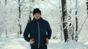 Ostente o homem que corre no parque da cidade do inverno durante o movimento da manhã vídeos de arquivo