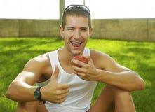 Ostente o homem que mostra a aprovação do sinal e que come uma maçã Fotos de Stock Royalty Free
