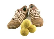 Ostente sapatas ao lado de 4 esferas de tênis Foto de Stock