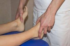 Osteopat som behandlar flickaanklar arkivfoto