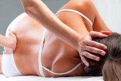 Osteopat som gör kranie- sacral övning på kvinna Arkivbilder
