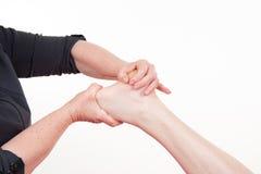 Osteopath που κάνει το μασάζ reflexology στο αρσενικό πόδι στο ζωηρόχρωμο κλίμα Στοκ Φωτογραφία
