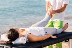Osteopath doing foot therapy on female foot outdoors. Royalty Free Stock Photography