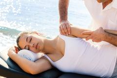 Osteopath doing shoulder manipulation massage on girl outdoors. Close up of male osteopath doing shoulder and arm therapy on young female athlete on location stock photos