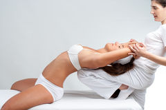 Osteopath doing spine treatment on woman. Royalty Free Stock Photos
